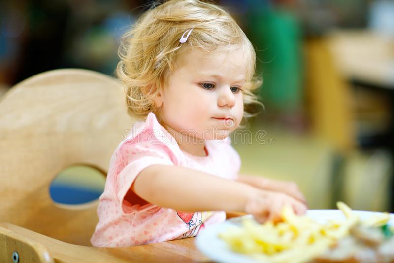 Adorable toddler girl eating healthy vegetables and unhealthy french fries potatoes. Cute happy baby child taking food. From dish at daycare or nursery canteen stock images