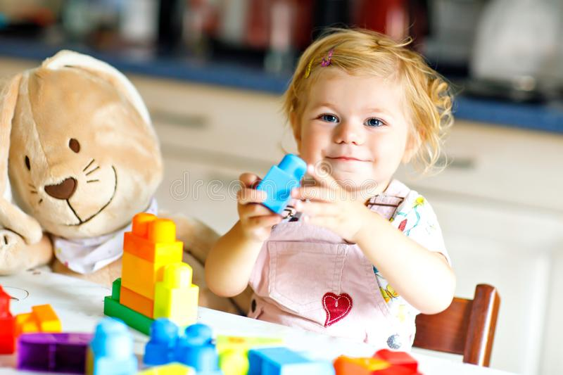 Adorable toddler girl with favorite plush bunny playing with educational toys in nursery. Happy healthy child having fun royalty free stock image