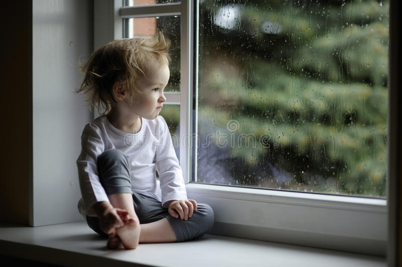 Adorable toddler girl looking at raindrops royalty free stock photos