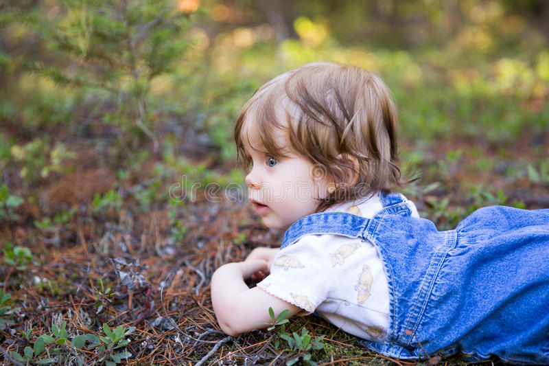 Adorable toddler girl lying on the ground with her face up royalty free stock photography