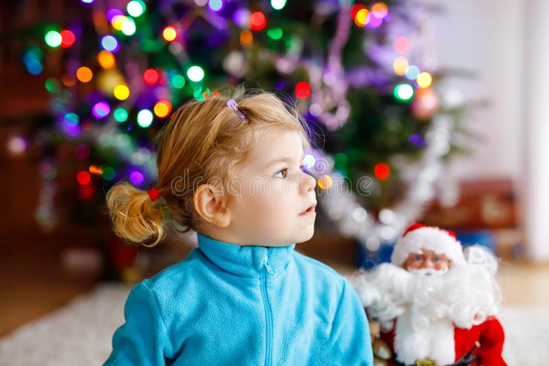 Adorable toddler girl playing with gifts and Christmas Santa Claus toys. Little child having fun with decorated and stock images