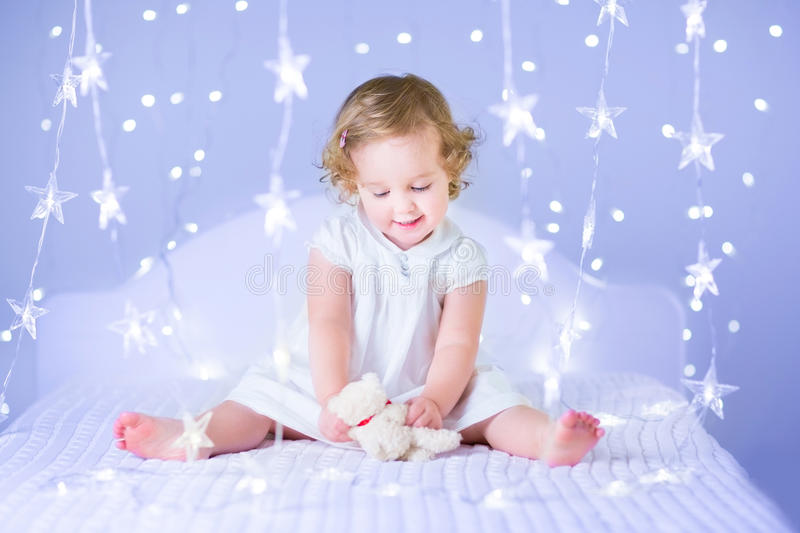 Adorable toddler girl playing with her toy bear between soft lights in star shape. Sweet toddler girl in a white dress with beautiful curly hair playing with her royalty free stock photo
