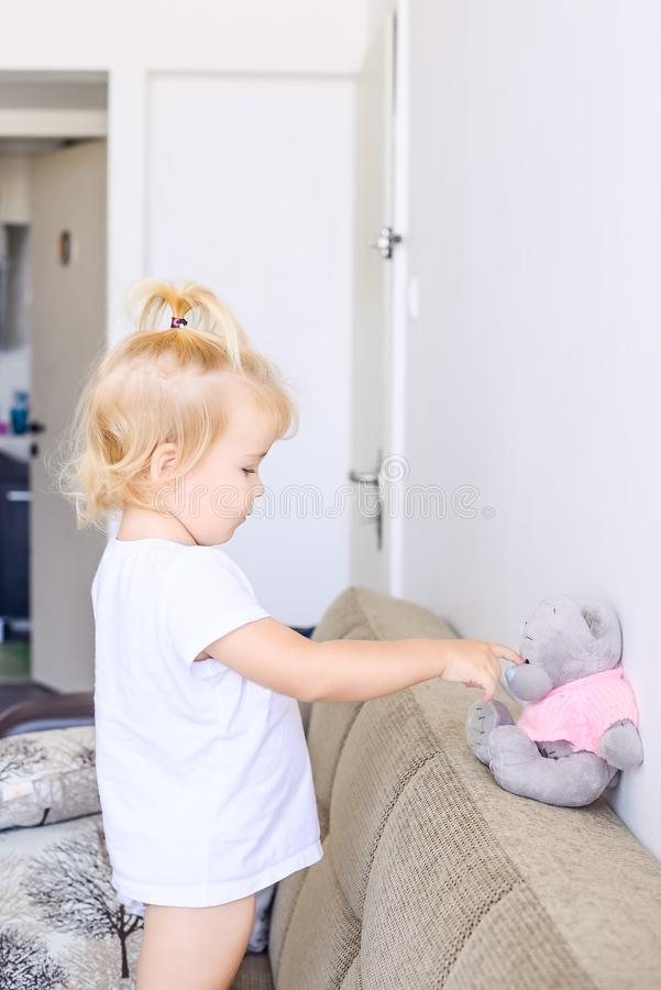 Adorable toddler girl playing with toy, teaching teddy standing on the sofa at home in white living room. Family, children educati stock images