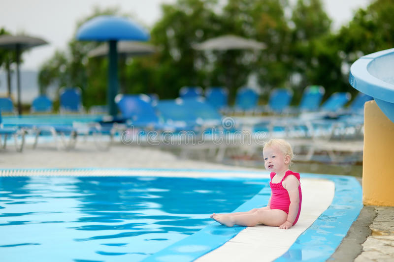 Adorable toddler girl sitting by a swimming pool. Cute toddler girl sitting by a swimming pool royalty free stock photography