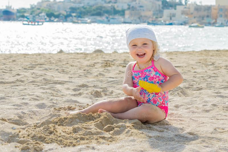 Adorable toddler girl smiling and playing on white sand beach seaside stock photos