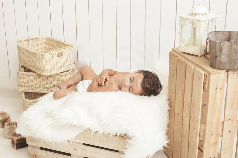 Adorable toddler sleeping on box with fur blanket royalty free stock photography