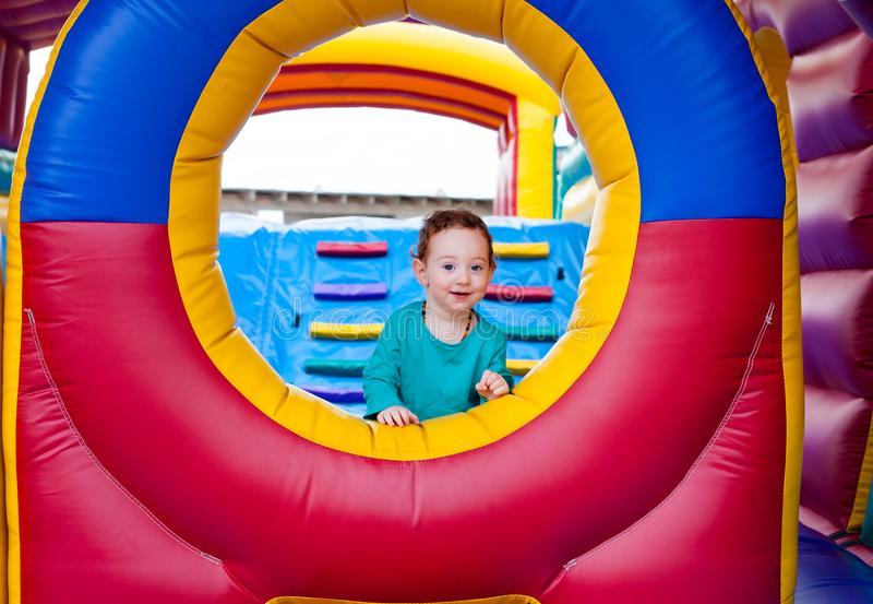 Adorable toddler on the trampoline. Adorable redhead toddler looking from a window on colorful trampoline castle royalty free stock image