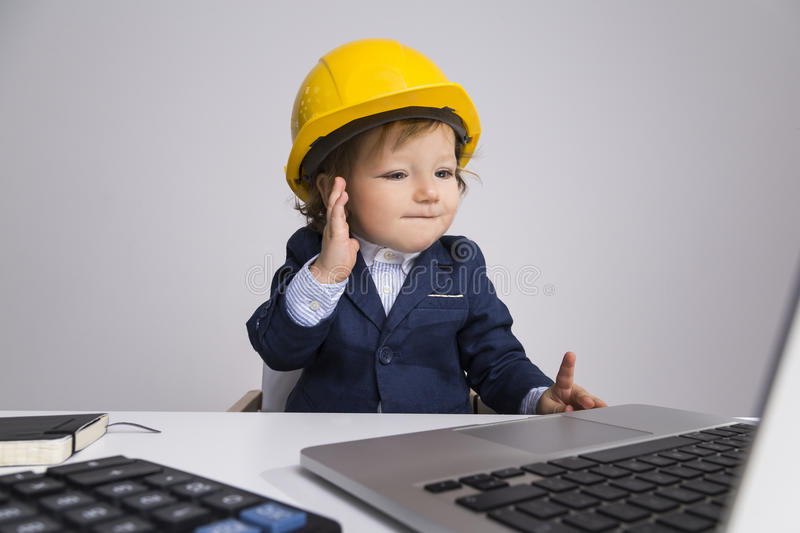 Adorable toddler in yellow construction helmet stock photo