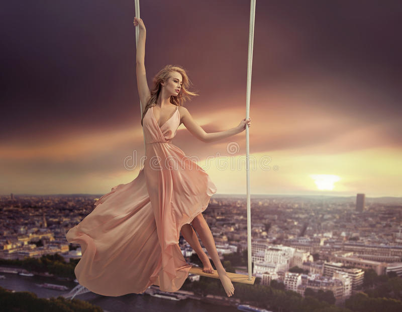 Adorable woman swinging above the city. Adorable woman dangling above the city