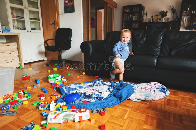Little boy portrait. Adorable 1 year old baby boy with funny facial expression playing in a very messy living room stock photos