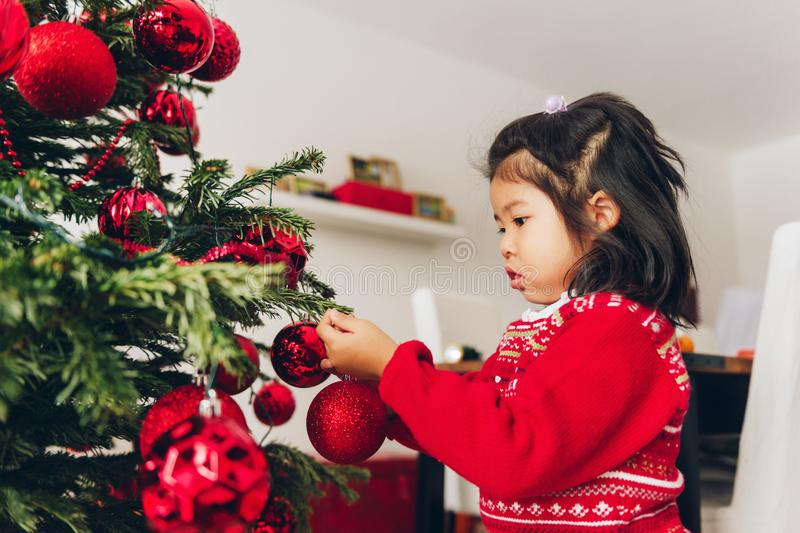 Adorable 3 year old toddler girl decorating Christmas tree royalty free stock photo