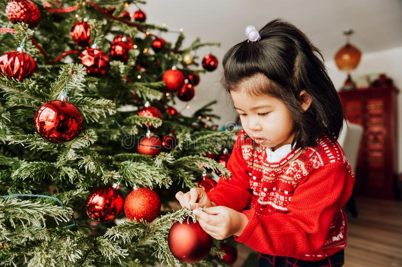 Christmas portrait of adorable 3 year old asian toddler girl wearing red Santa dress and hat royalty free stock photo