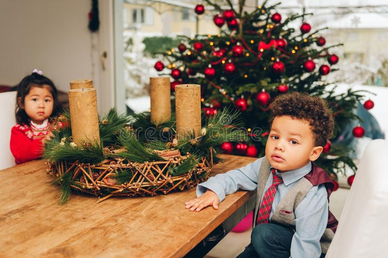 Two adorable 3 year old kids playing by the Christmas tree royalty free stock images