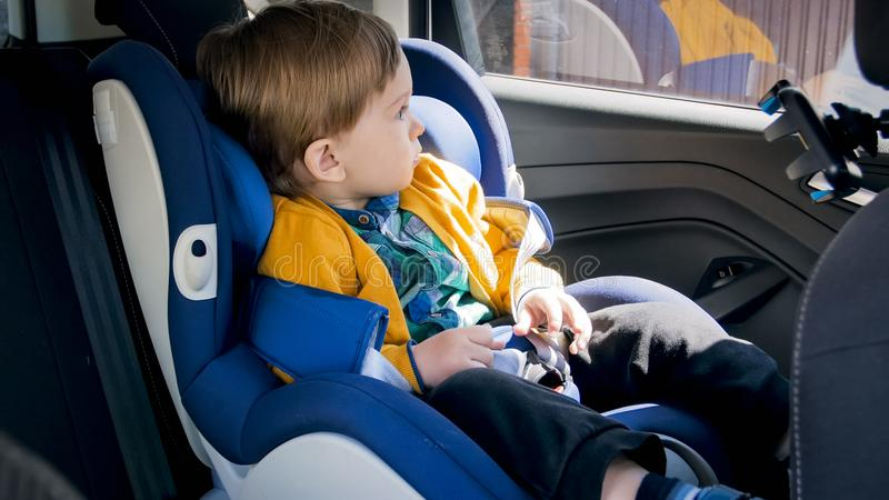 Adorable 2 years old baby boy sitting in car safety seat and looking out of the window stock images