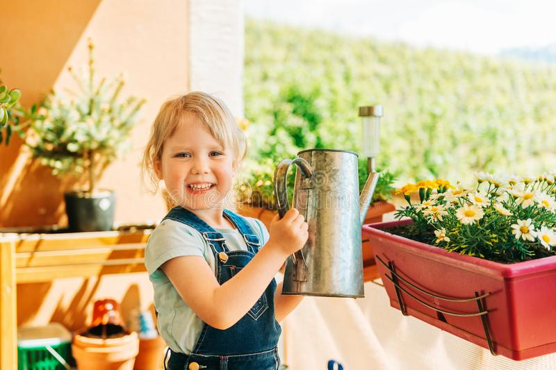 Adorable 3-4 years old kid girl watering yellow daisy flowers on sunny balcony stock photo