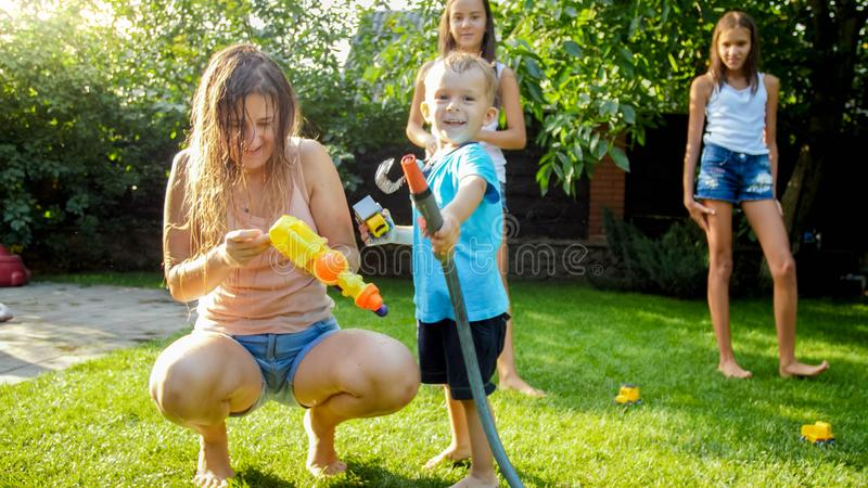 Adorable 3 years old toddler boy splashing water from plastic toy gun at house backyard. Children playing and having fun stock photography