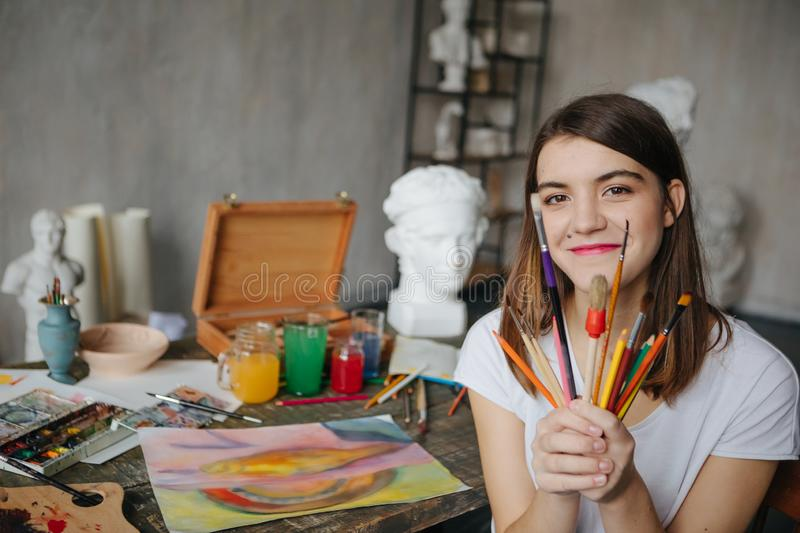 Adorable young artist girl holding brushes and smiling. Creative workshop room at the background. Happy moments stock images