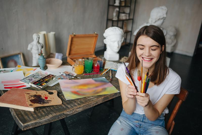 Adorable young artist girl holding brushes and smiling. Creative workshop room at the background. Happy moments. Inspiration mood royalty free stock photos