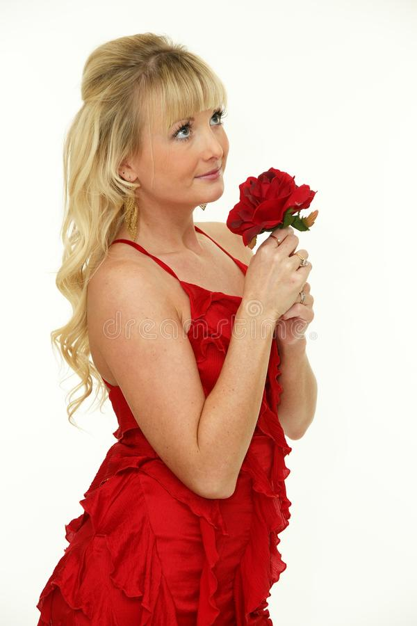 Adorable young blonde woman with red rose stock photos