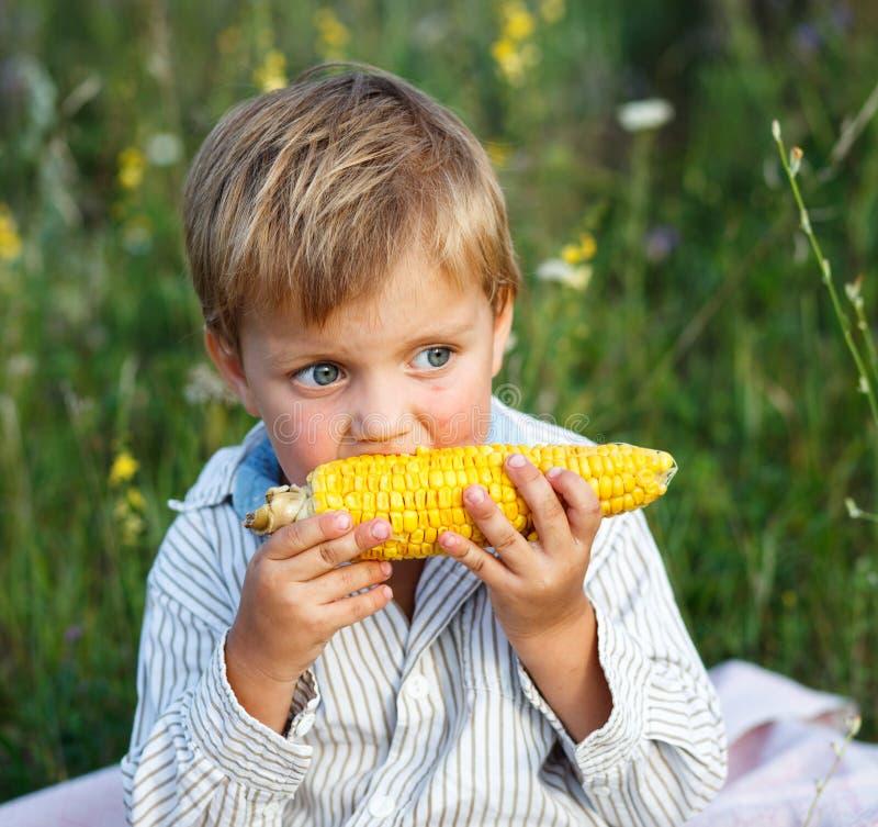 Adorable young boy eating corn on the cob stock photos