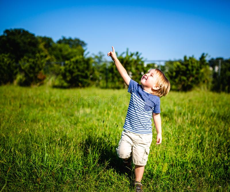 Young Boy in a Field Points to the Sky stock photography