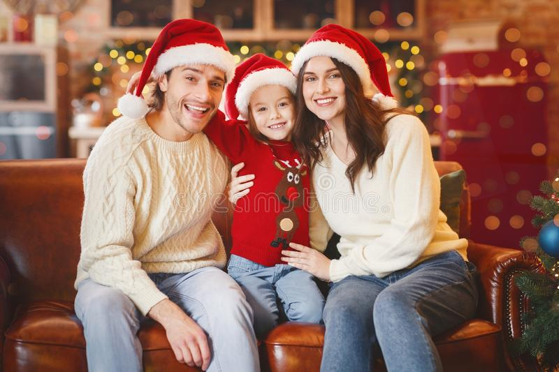 Adorable young family posing in santa hats over decorated background stock image