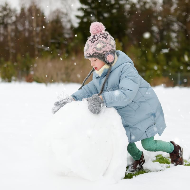 Adorable young girl building a snowman in the backyard. Cute child playing in a snow royalty free stock image