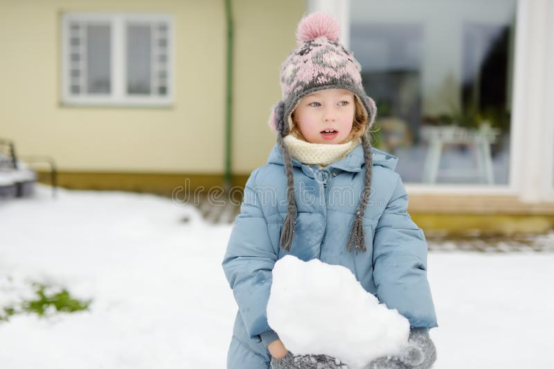 Adorable young girl building a snowman in the backyard. Cute child playing in a snow stock photo