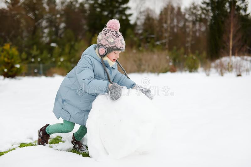 Adorable young girl building a snowman in the backyard. Cute child playing in a snow stock image