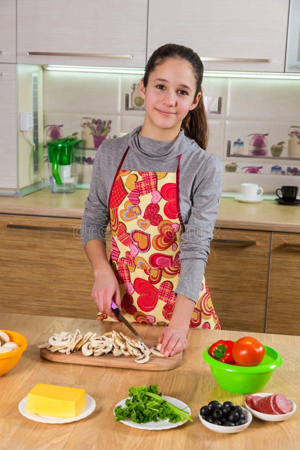 Adorable young girl cut the mushrooms in kitchen stock photo