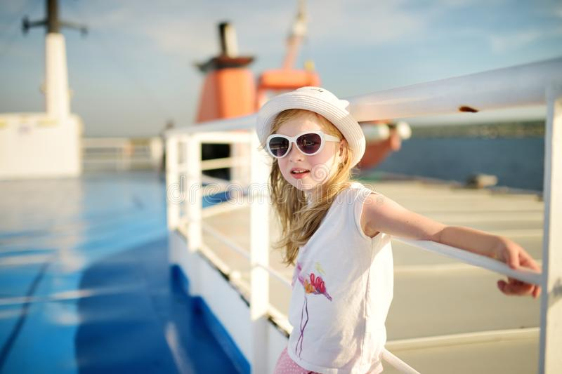 Adorable young girl enjoying ferry ride staring at the sea on sunset. Child having fun on summer family vacation in Greece. Kid sailing on a boat stock photos