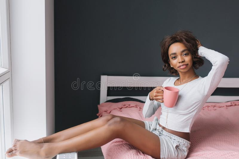 Adorable young girl enjoying morning on bed next to window, holding coffee, tea in room with gray wall, pink carpet on royalty free stock photos