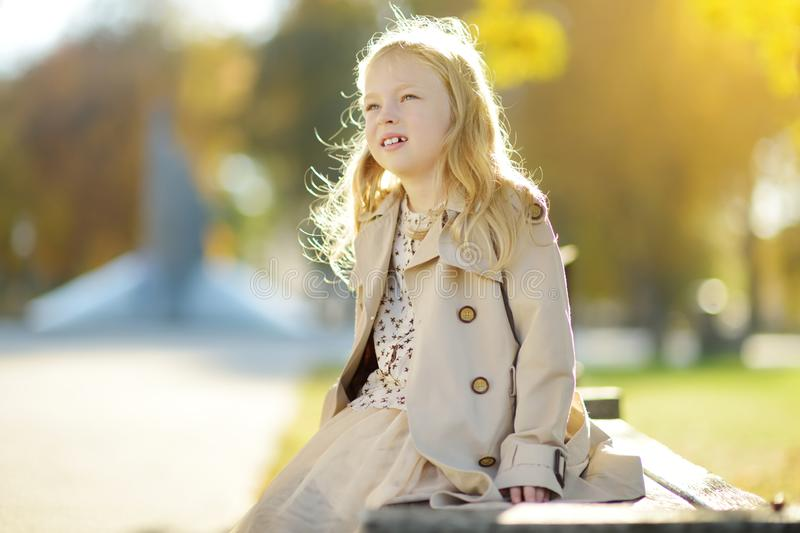 Adorable young girl having fun on beautiful autumn day. Happy child playing in autumn park. Kid gathering yellow fall foliage royalty free stock images