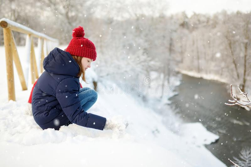 Adorable young girl having fun in beautiful winter park. Cute child playing in a snow. Winter activities for family with kids stock images