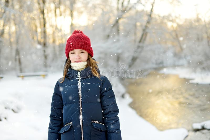 Adorable young girl having fun in beautiful winter park. Cute child playing in a snow. Winter activities for family with kids stock image