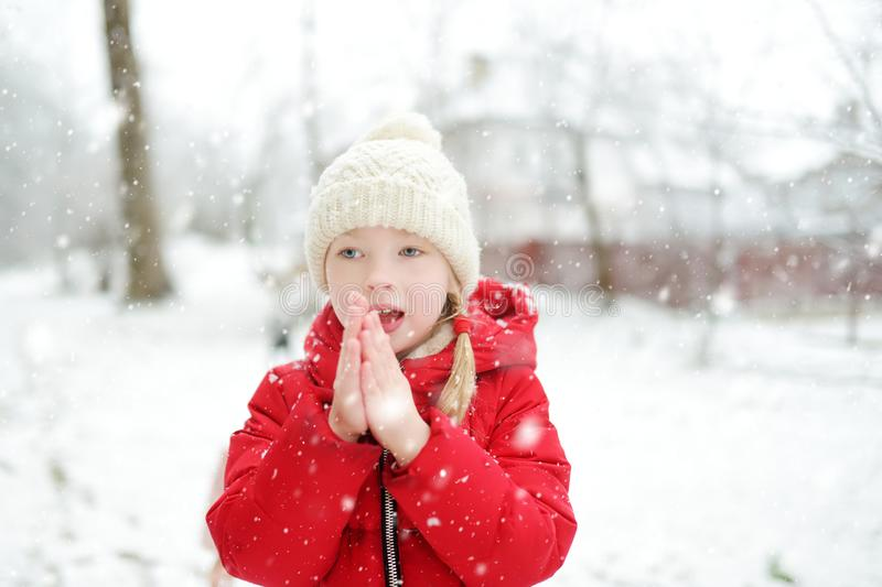 Adorable young girl having fun in beautiful winter park during snowfall. Cute child playing in a snow stock image
