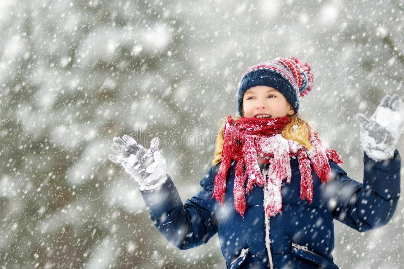 Adorable young girl having fun in beautiful winter park during snowfall. Cute child playing in a snow stock images