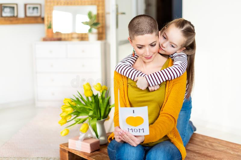 Adorable young girl and her mom, young cancer patient, reading a homemade greeting card. Family concept. Happy Mother`s Day. Adorable young girl and her mom royalty free stock photo