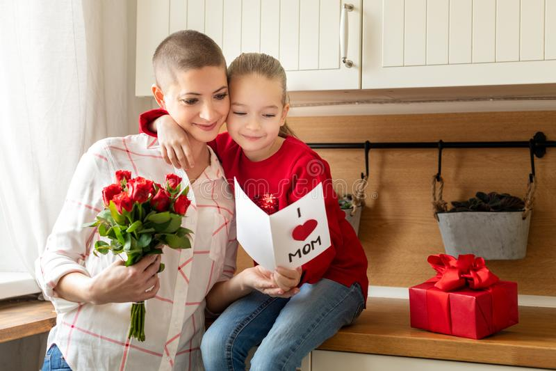 Adorable young girl and her mom, young cancer patient, reading a homemade greeting card. Family concept. Happy Mother`s Day. stock photo