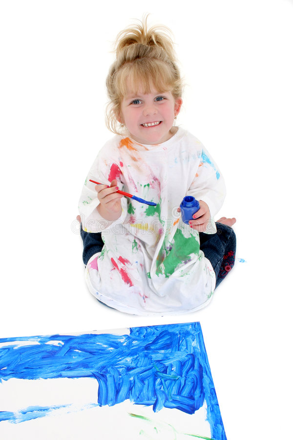 Adorable Young Girl Painting Poster Board on Floor. Shot in studio over white royalty free stock image