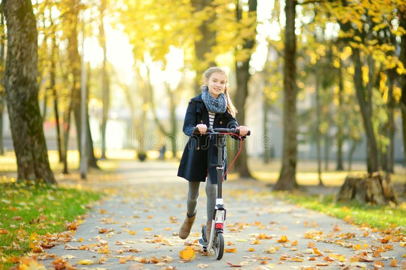 Adorable young girl riding her scooter in a city park on sunny autumn evening. Pretty preteen child riding a roller royalty free stock image