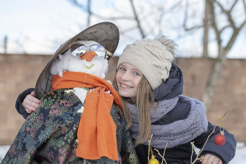 Adorable young girl with a snowman in beautiful winter park. Winter activities for children. stock image