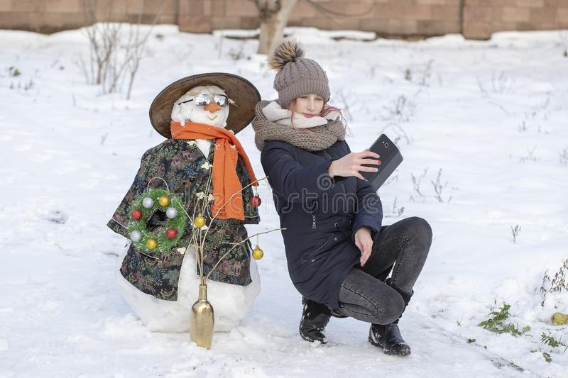 Adorable young girl is taking pictures of selfie with a snowman in beautiful winter park. Winter activities for children. royalty free stock photos