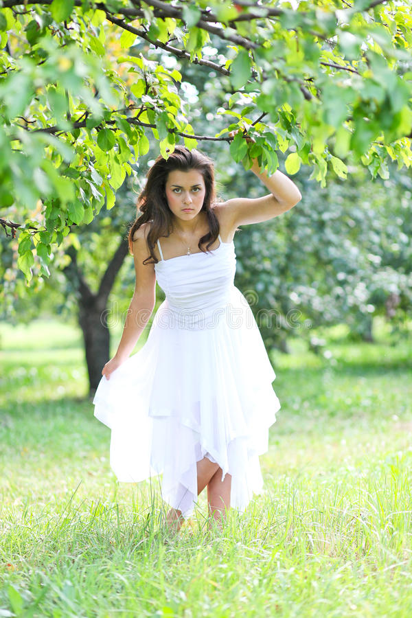 Adorable young girl in white clothes enjoying stock photo