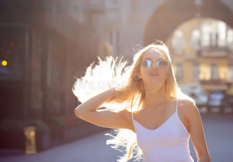 Adorable young model with long hair wearing glasses, posing at the passage in rays of sun. Copy space stock images