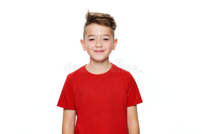 Adorable young teenage boy waist up studio portrait isolated over white background. Handsome boy looking at camera with smile. stock photo