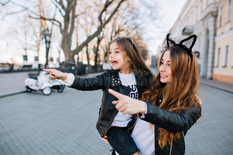 Adorable young woman with her daughter saw something interesting on the other side of the street. Amazed little girl in stock photo