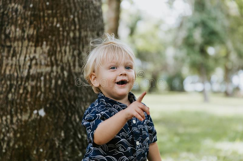 Adorably Happy and Cute Little Caucasian Toddler Baby Boy with Long Blond Hair Laughing, Playing, and Running Outside in Green Nat stock photography