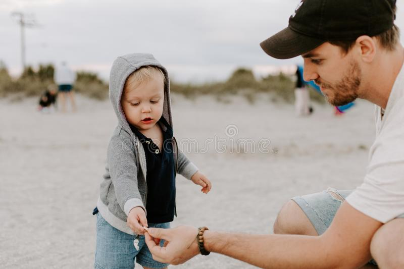 Adorably Perfect Young Father and Baby Toddler Son Family Having Fun Time at the Sandy Beach During Sunset Outside By the Ocean Wa royalty free stock photos