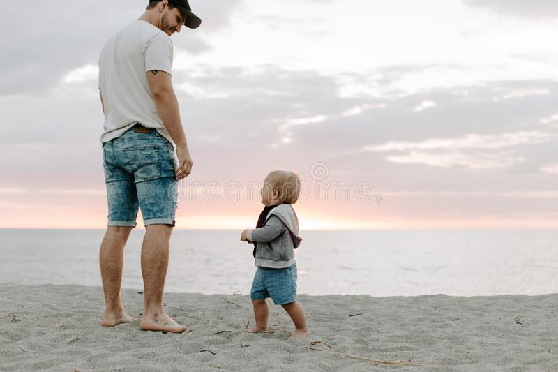 Adorably Perfect Young Father and Baby Toddler Son Family Having Fun Time at the Sandy Beach During Sunset Outside By the Ocean Wa stock photography